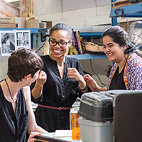 Photo of three students laughing and gesturing in a workshop.