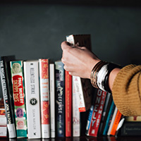 Photo of hand reaching for a book on a shelf.